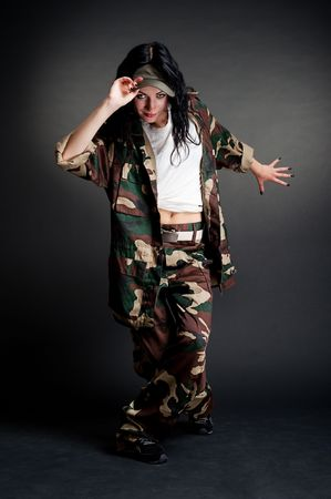 military girl dancing against dark background photo