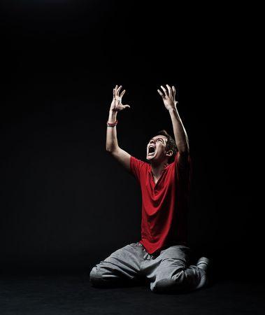 wanhopig: erg emotioneel foto. jonge man te huilen in de duisternis Stockfoto