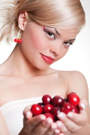 young pretty blonde with cherries against white background photo