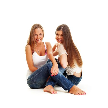 two happy girls in jeans sitting on the floor. isolated on white photo