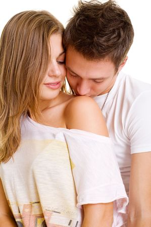 flirt: young man kissing girl in the shoulder. isolated on white
