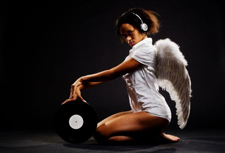 beautiful angel with vinyl against dark background Stock Photo