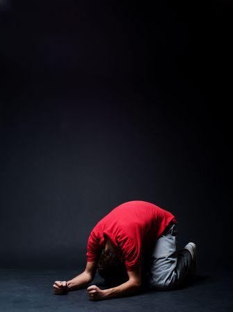 woe: desperate man praying  in darkness Stock Photo