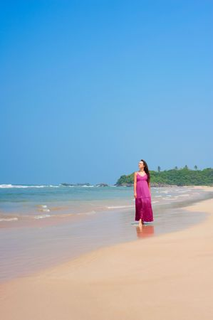 pleasant woman in pink long dress walking at the beach photo
