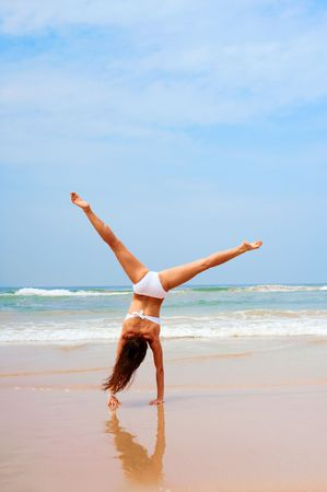 woman in white swimsuit doing cartwheel at the beach photo
