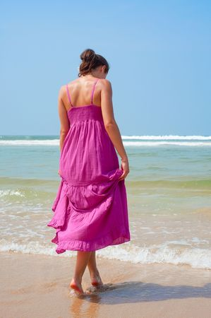 attractive woman in long dress walking in to the ocean photo