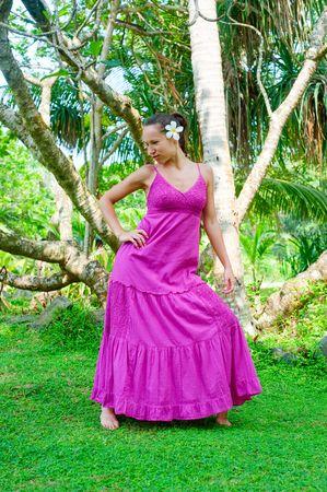 beautiful model in long dress posing against exotic trees photo
