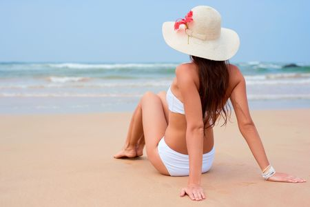 beautiful woman in white hat sitting at the beach photo
