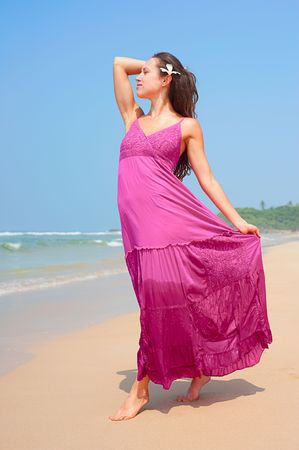 magenta dress: graceful woman in long dress walking at the beach