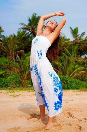 happy carefree woman in dress standing in the sand photo