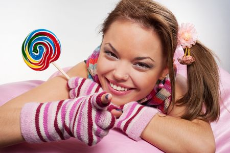 sugarplum: smiley woman with motley lollipop pointing Stock Photo