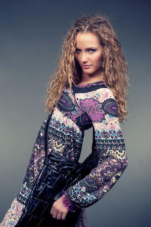 ethnic dress: moda ragazza in abito etnica posa contro lo sfondo grigio