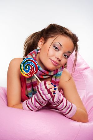 sugarplum: lively girl with sugarplum lying on the pink chair Stock Photo