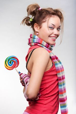 sugarplum: playful girl with lollipop posing against grey background Stock Photo