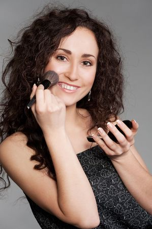 smiley attractive woman with powder and brush photo