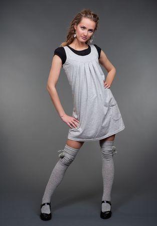 graceful blonde in grey dress posing against dark background