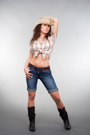 sexy cowgirl posing against grey background photo