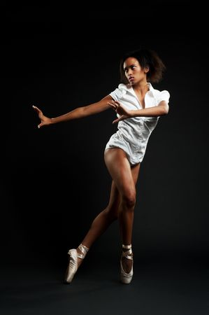 alluring ballerina in white shirt dancing against black background Stock Photo - 6193368