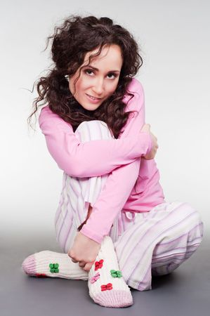 smiley young woman in pink pyjamas sitting on the floor photo