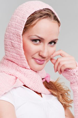portrait of pretty blonde in pink scarf against grey background photo