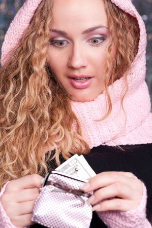 amazed woman in pink scarf looking at her purse  photo