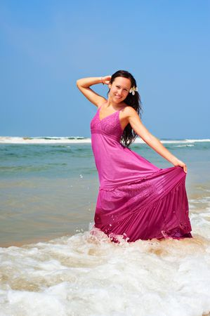 cheerful woman in pink dress standing in ocean photo