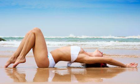traje de bano: hermosa mujer tumbada en la arena h�meda contra el cielo azul y el Oc�ano