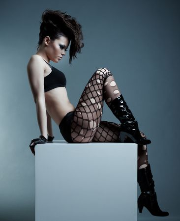 fashionable model with hairstyle sitting on the cube Stock Photo