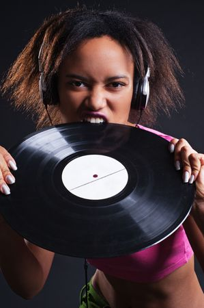 sexy headphones: portrait of attractive woman with vinyl against dark background
