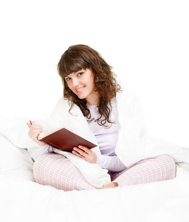 beautiful girl reading book in her bed photo