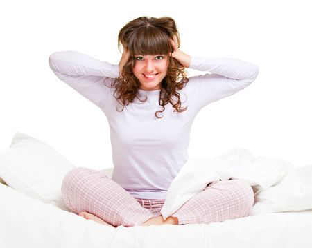 cheerful girl in pajamas sitting in bed photo
