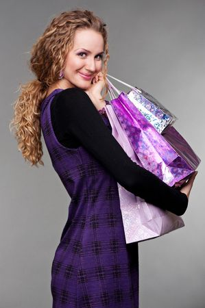 portrait of happy woman with purchases against grey background photo