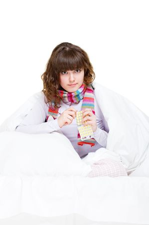 ill girl in scarf holding yellow pills photo