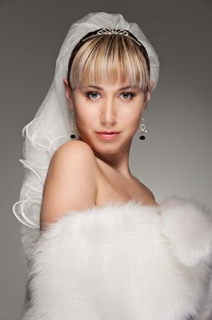 beautiful bride in white fur posing against grey background photo