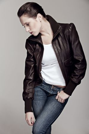 model in leather jacket and jeans posing against grey background photo