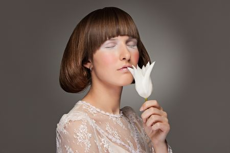 portrait of model with white tulip against grey background photo