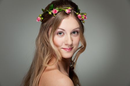 portrait of cheerful woman with roses on the hair photo