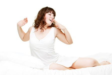 luxuriate: pretty young woman in nightie waking up and yawning