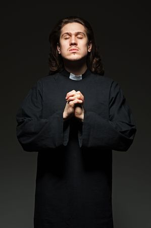 clergyman: young priest is praying against dark background