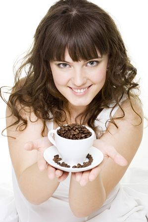 smiley young woman holding white cup of coffee beans photo