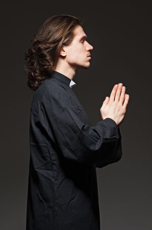 clergyman: young priest in black coat is praying against dark background