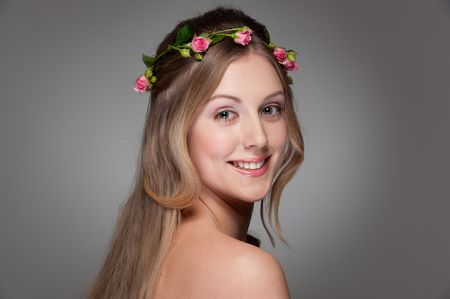 portrait of graceful young woman with roses on her head photo