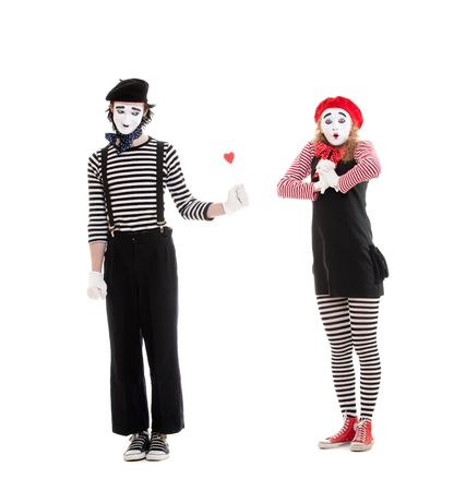 pantomime: portrait of mimes. man giving small red heart to amazed woman. isolated on white background Stock Photo