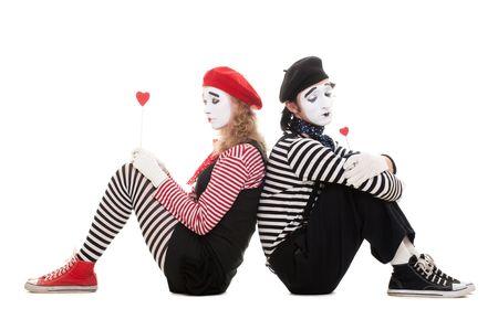 pantomime: Retrato de mimos. amantes tristes sentada en el suelo con corazones peque�o rojo. aislados en blanco