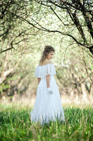 beautiful blonde in white dress walking in forest photo
