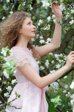 portrait of lovely blonde in blossoming orchard photo