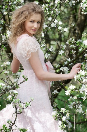 lovely young woman posing near blossoming tree photo
