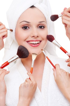 many hands applying make-up to beautiful smiley woman photo