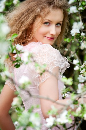 beautiful smiley model posing in white flowers  photo