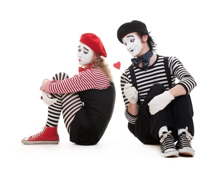 portrait of mimes. smiley man giving heart to sad woman. isolated on white background photo